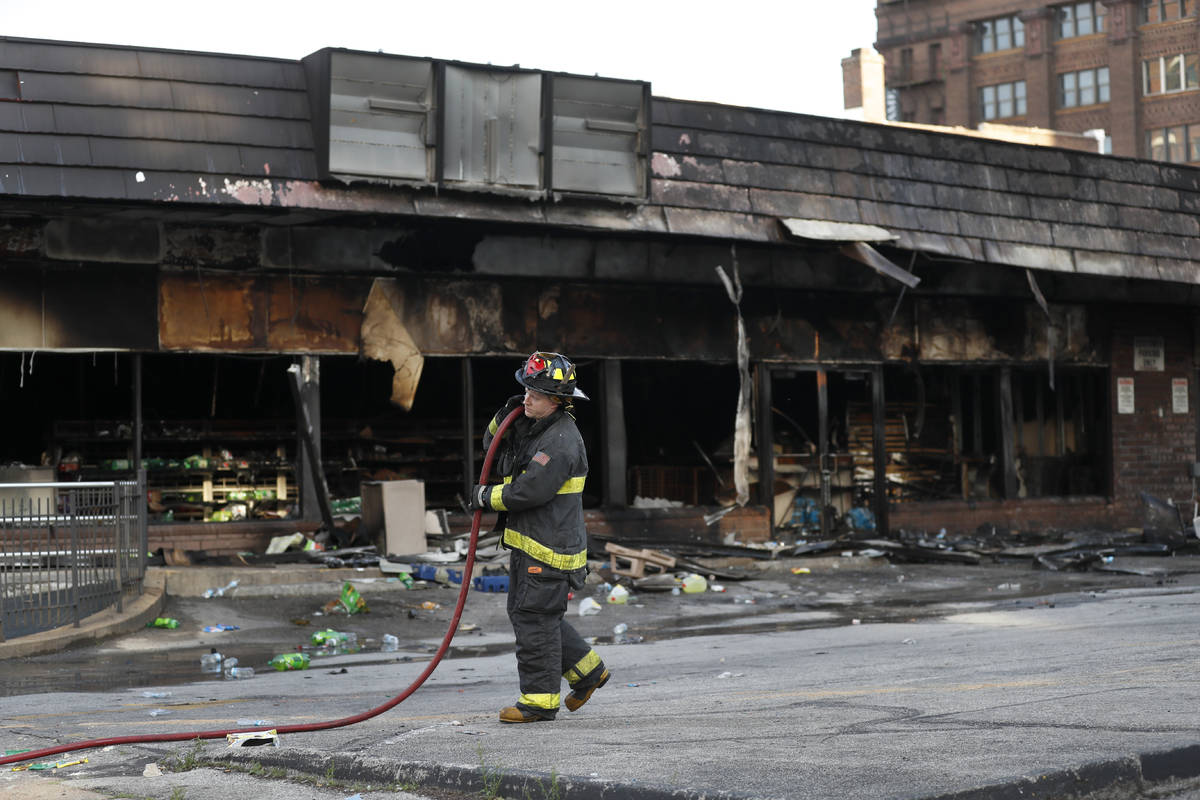 A member of the St. Louis Fire Department removes a hose outside a vandalized and burned conven ...