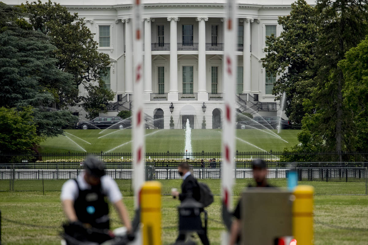 The White House is visible as uniformed Secret Service agents stand at a checkpoint on Constitu ...