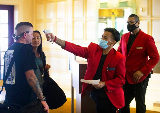 Security officers Rowell Briones, middle, and Chandler Moon, take guests temperatures before al ...