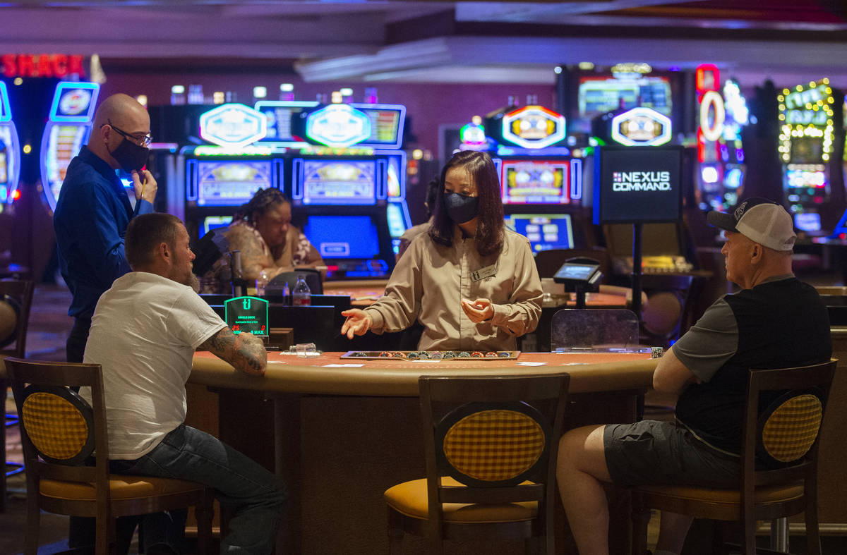 Gamblers play blackjack with empty seats on each side to maintain social distancing at TI on Th ...
