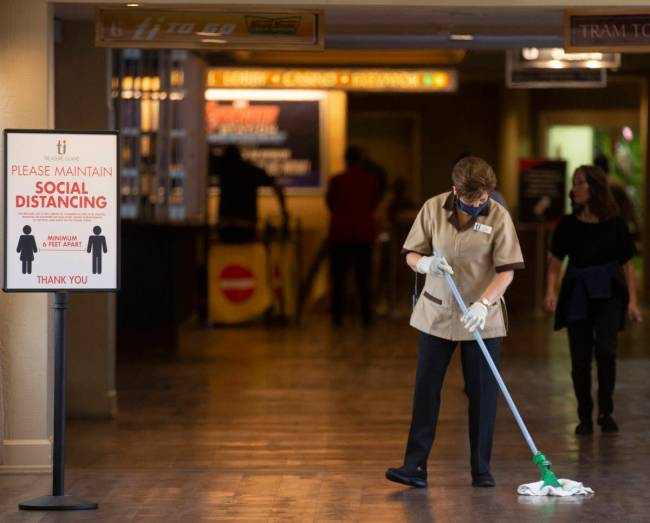 Housekeeping staff mop the floor next to a sign reinforcing social distancing at TI on Thursday ...