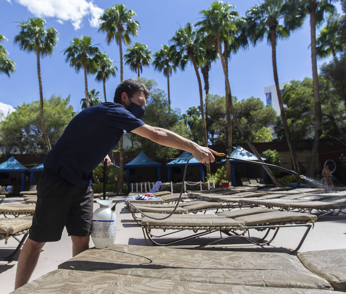 Cabana Host Cristian Elorza sprays sanitizer on pool chairs at TI on Thursday, June 4, 2020, in ...