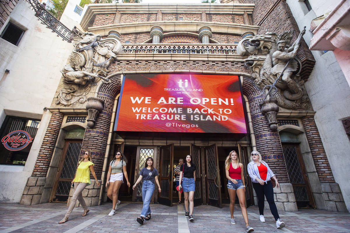 Guests walk under a large sign welcoming tourists back to TI on Thursday, June 4, 2020, in Las ...