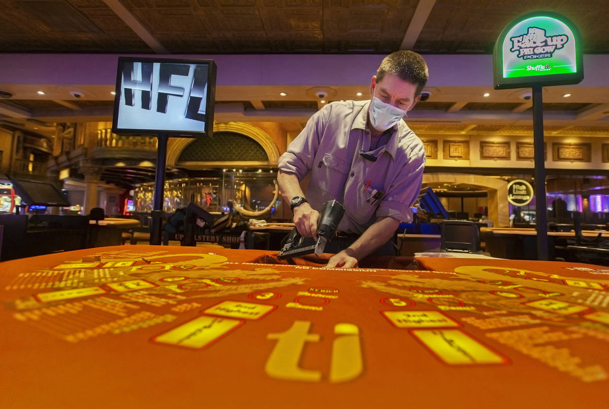 Facility technician Paul Burnett replaces the layouts on the Face Up Pai Gow poker tables on Mo ...