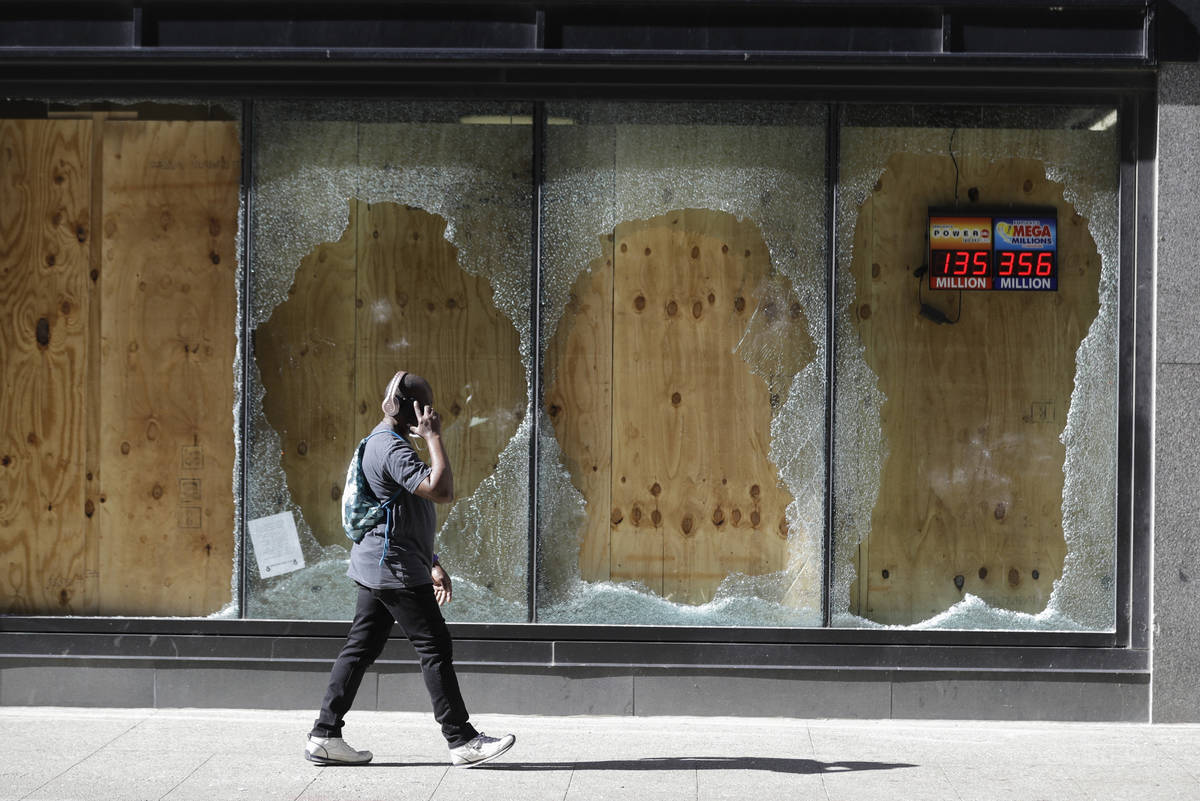 A man walks past broken and boarded up windows at a CVS store in downtown Louisville, Ky., Tues ...