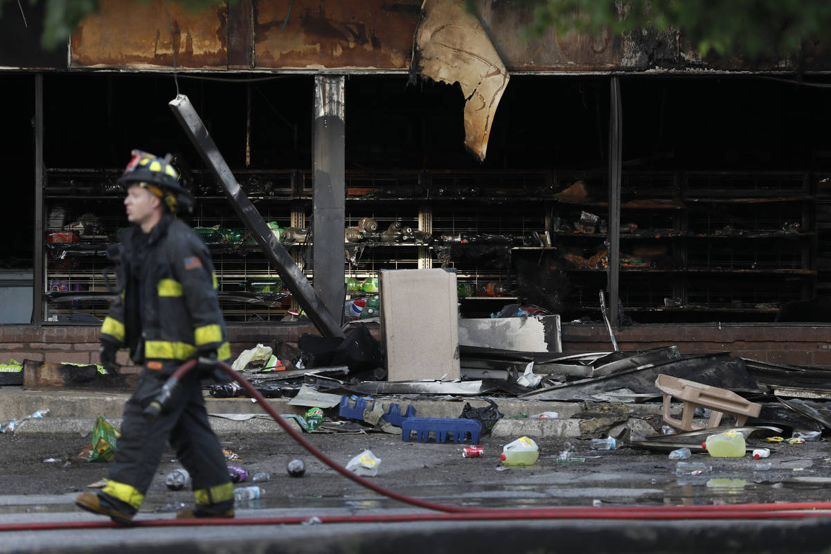 A member of the St. Louis Fire Department wraps up their work outside a vandalized and burned c ...