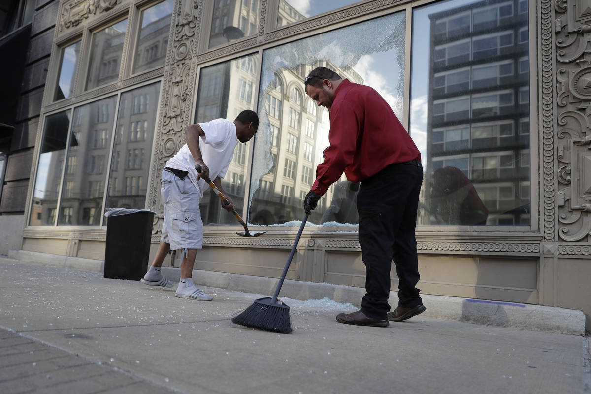 Kenneth Snelson, left, helps Dan Wilding clean up glass from a broken window, Tuesday, June 2, ...