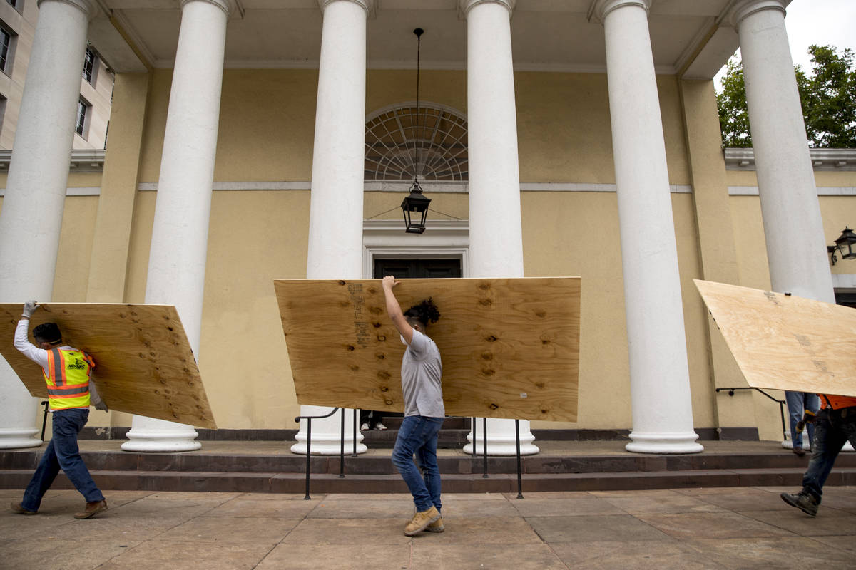 Workers carry large wood boards past the historical St. John's Episcopal Church across Lafayett ...