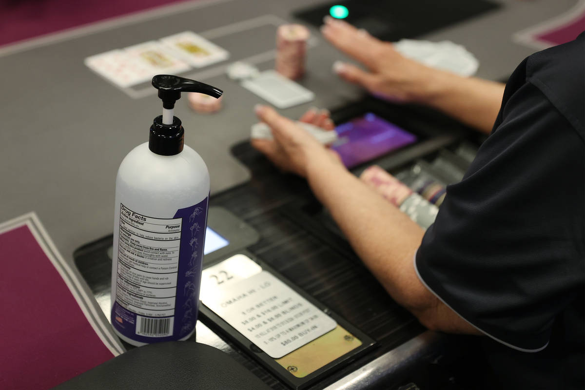 A hand sanitizer bottle sits on a poker tables during the first day of reopening at The Orleans ...