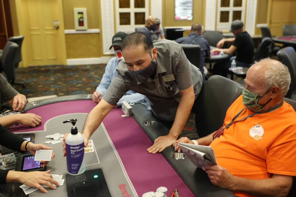 Poker shift manager Kenneth Davis deliver a new bottle of Gand sanitizer to a table in the poke ...