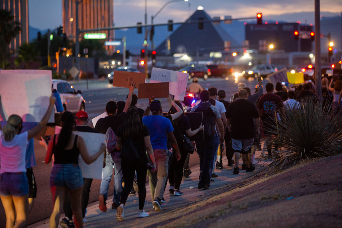 Protesters march with the Strip in the distance during a Black Lives Matter protest at UNLV in ...