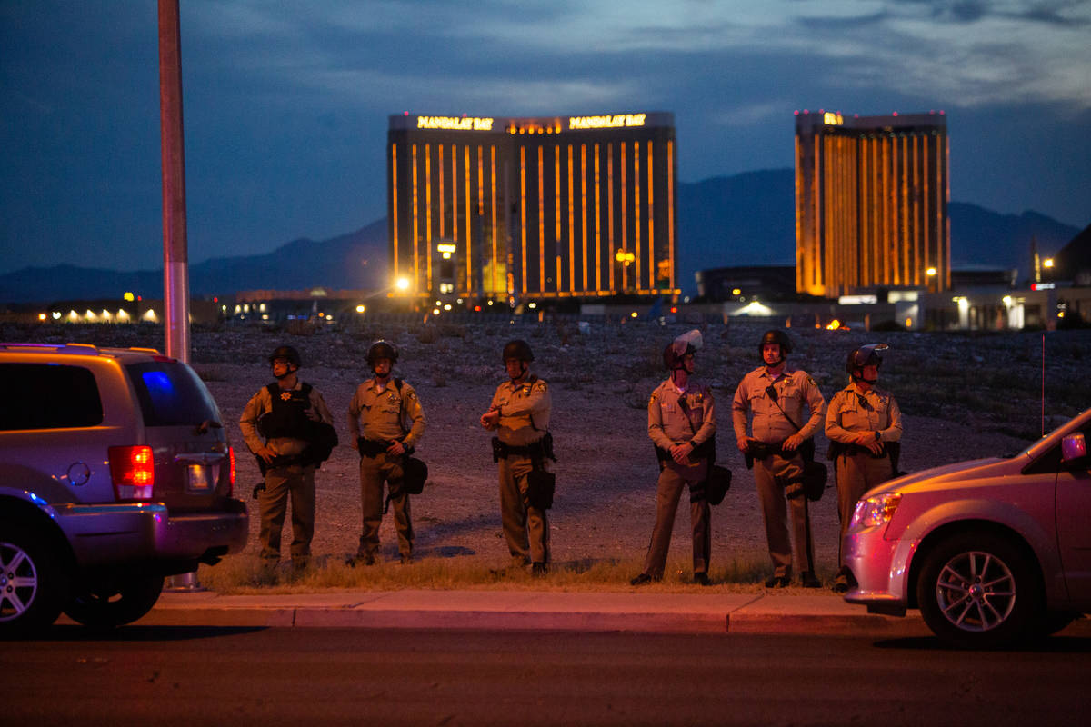 Las Vegas police watch protesters march with the Strip in the distance during a Black Lives Mat ...