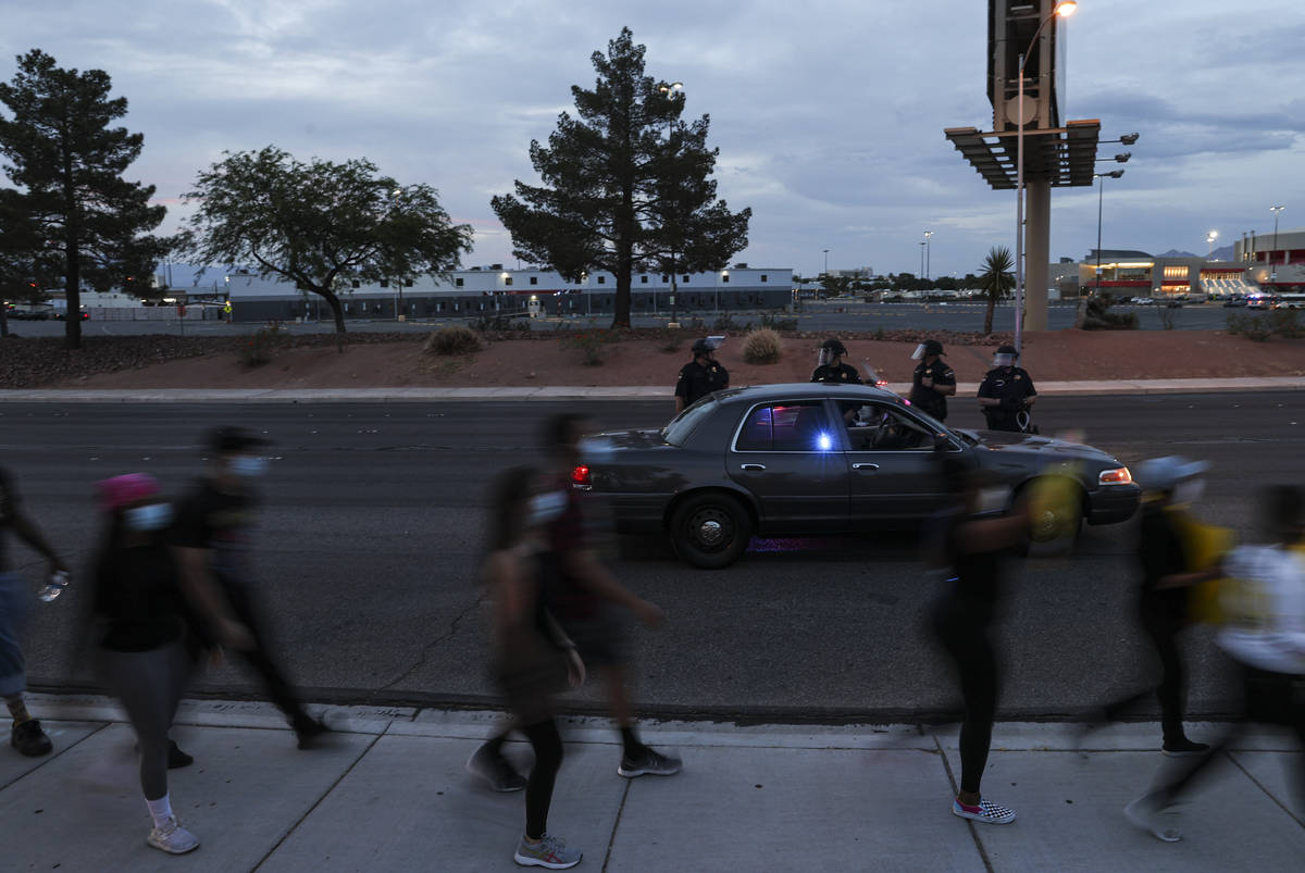 Police watch as people march during a Black Lives Matter protest near UNLV in Las Vegas on Tues ...