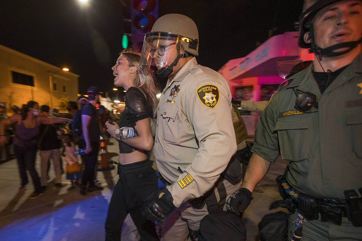 Las Vegas Police officers detain a protester from a Black Lives Matter march at Container Park ...