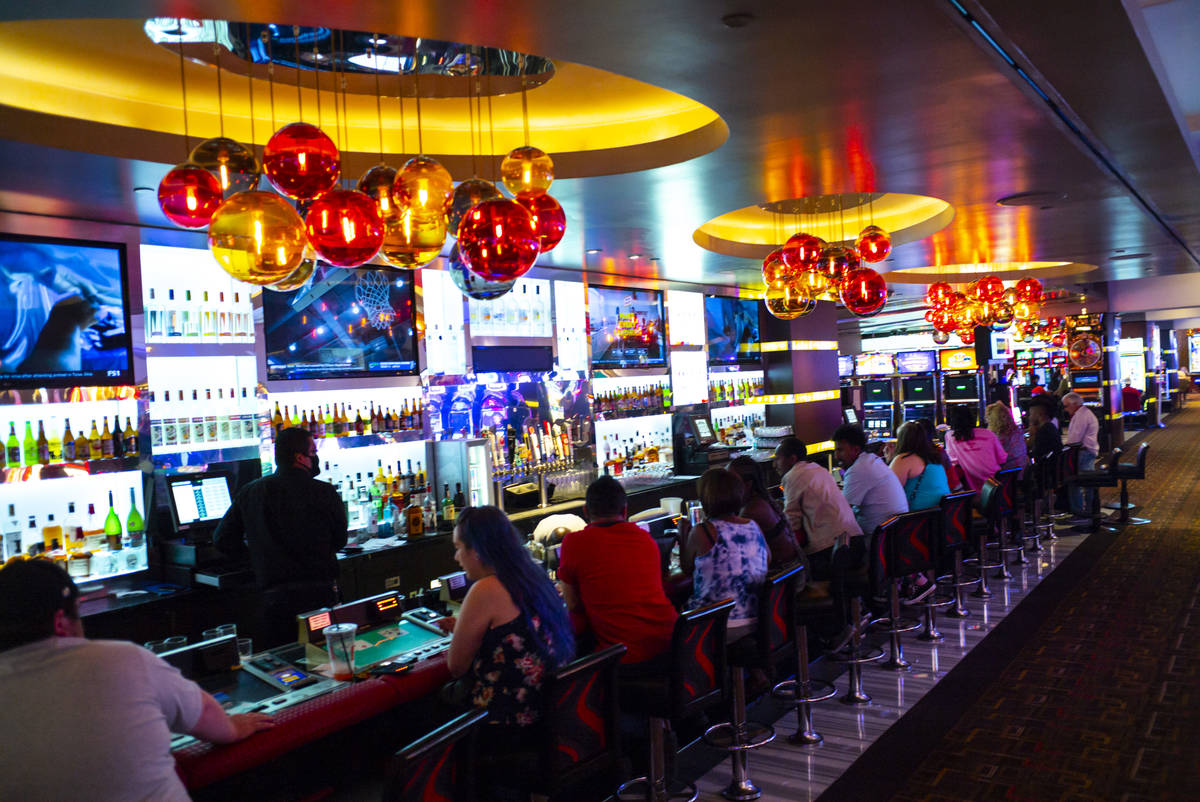 People drink and play bartop gaming machines at the Golden Nugget as hotel-casinos reopen in do ...