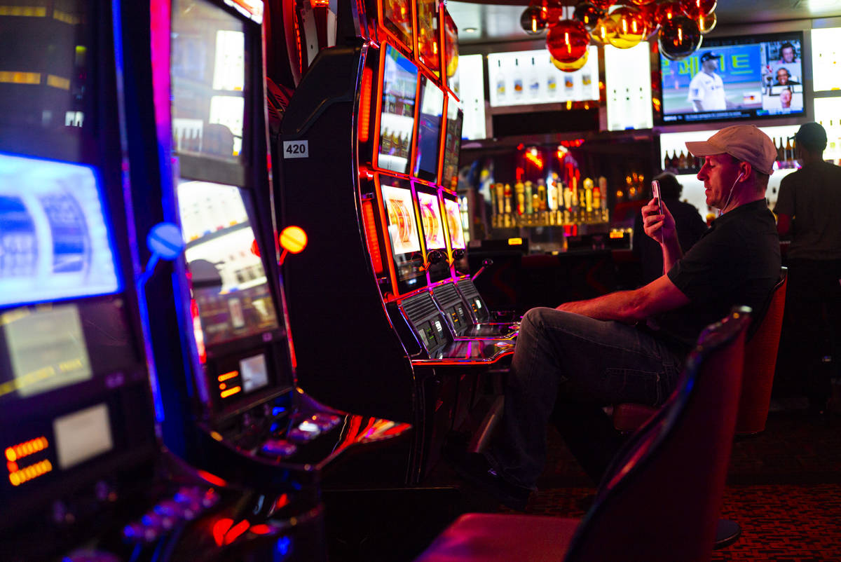 A man records while playing slots at the Golden Nugget as hotel-casinos reopen in downtown Las ...