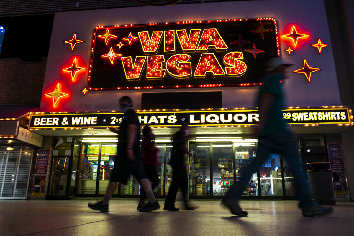 People walk past the Viva Vegas gift shop at the Fremont Street Experience as hotel-casinos reo ...