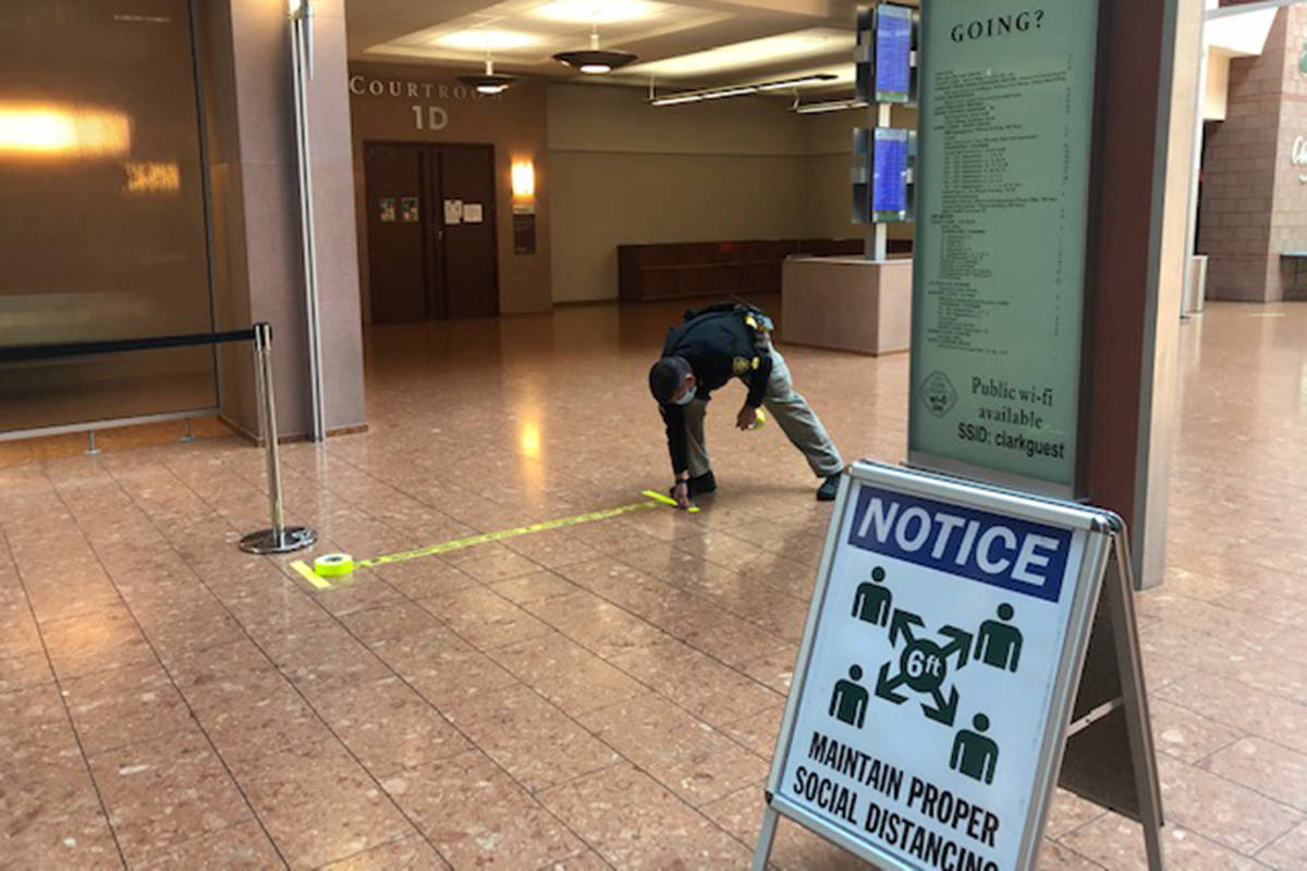 A marshal lays tape along the first floor of the Regional Justice Center on Friday, May 29, 202 ...