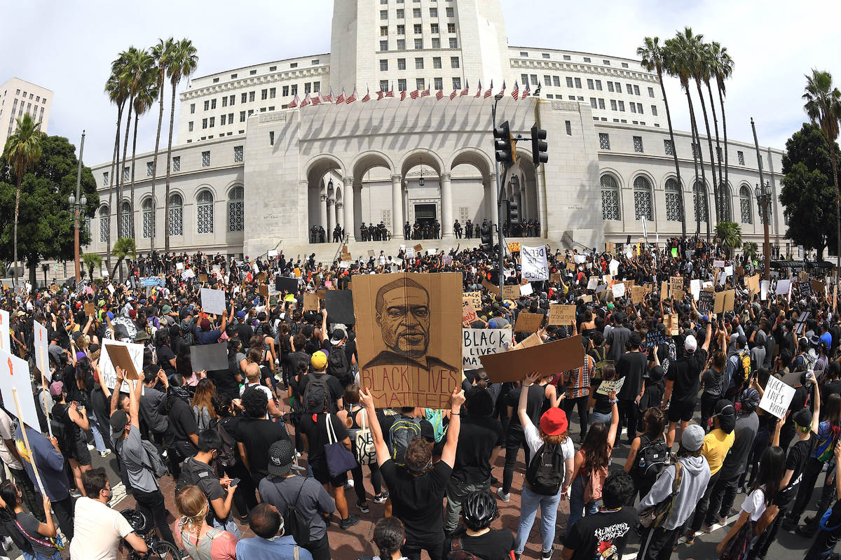 In this photo taken with a wide angle lens, demonstrators stand in front of Los Angeles City Ha ...