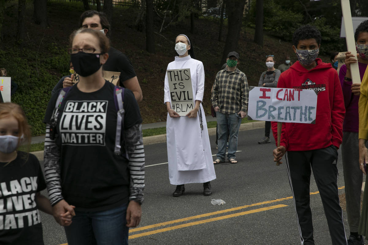 Sister Quincy Howard, center, a Dominican nun, protests the arrival of President Donald Trump t ...