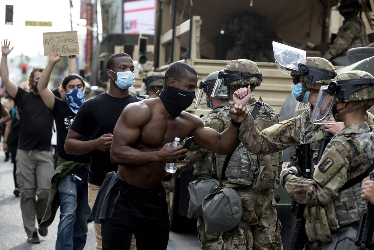 Demonstrators greet members of the National Guard as they march along Hollywood Boulevard, Tues ...