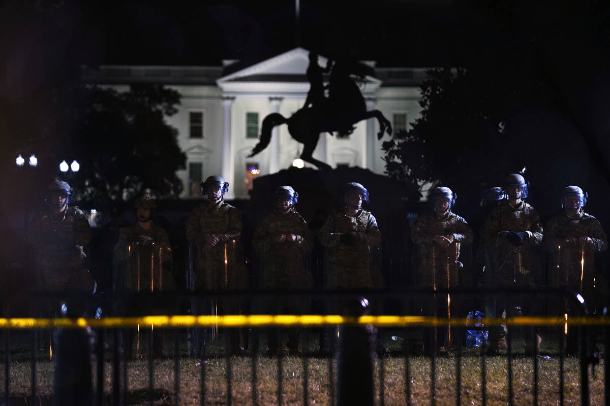 With the White House in the background, a line of police forms behind a fence in Lafayette Park ...