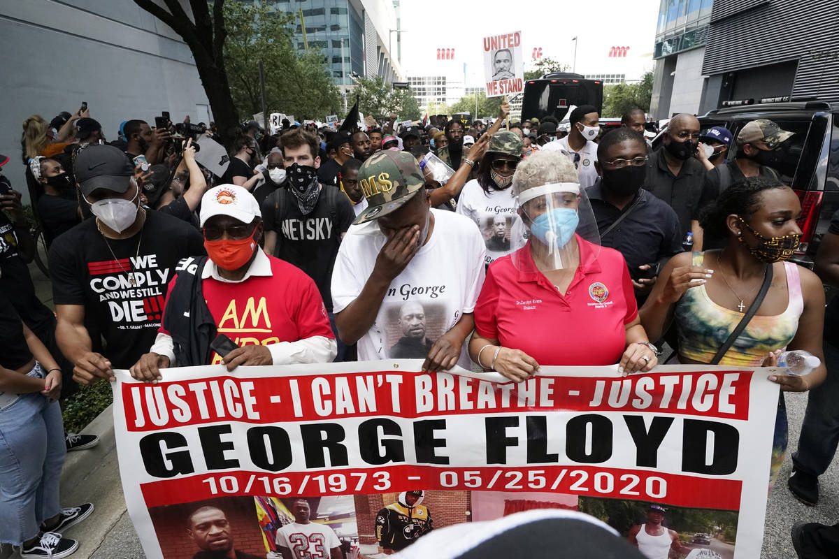 LaTonya Floyd, third from left, participates in a march to protest the death of her brother, Ge ...