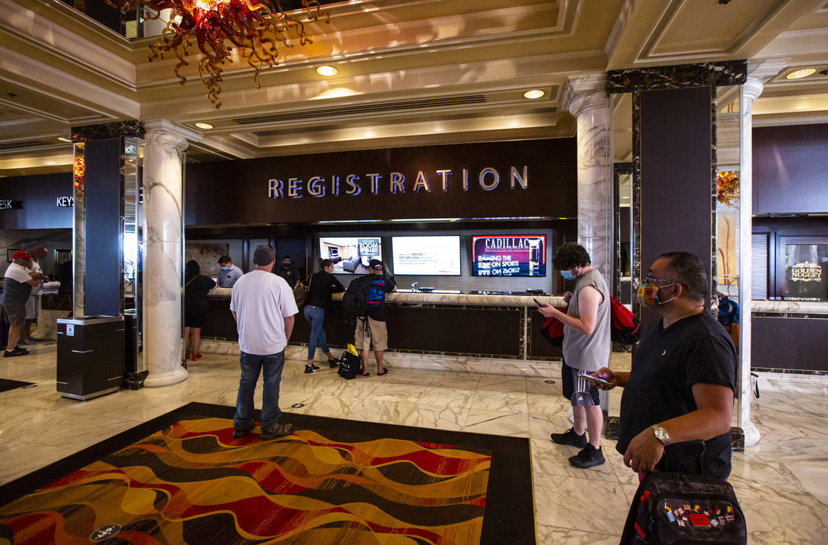 Guests line up while social distancing for check-in at the Golden Nugget in downtown Las Vegas ...
