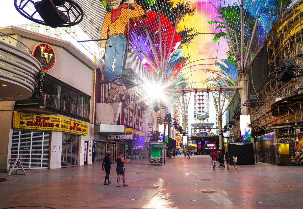 People walk around the Fremont Street Experience as hotel-casinos reopen in downtown Las Vegas ...