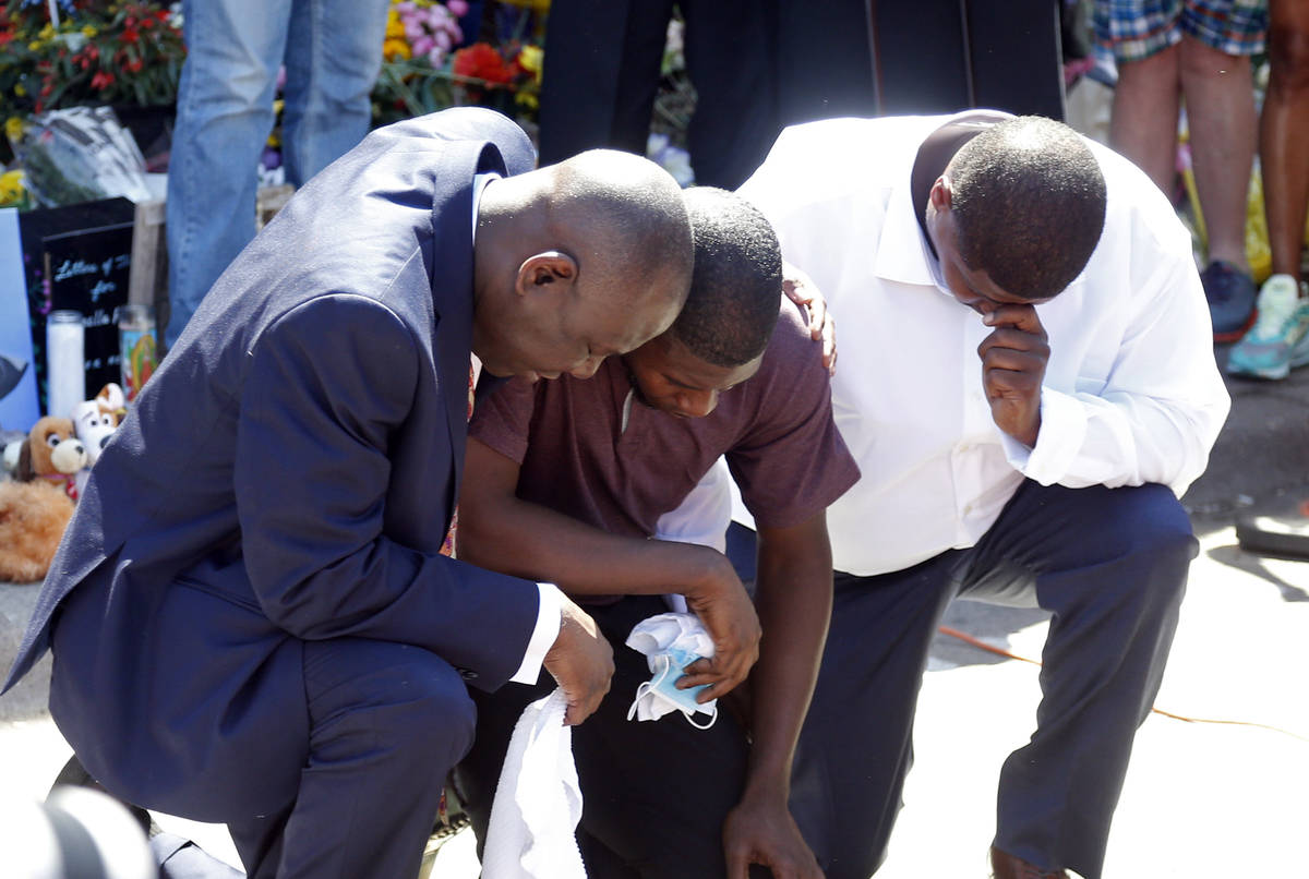 Quincy Mason, center, the son of George Floyd, and family attorney Ben Crump, left, kneel, Wedn ...