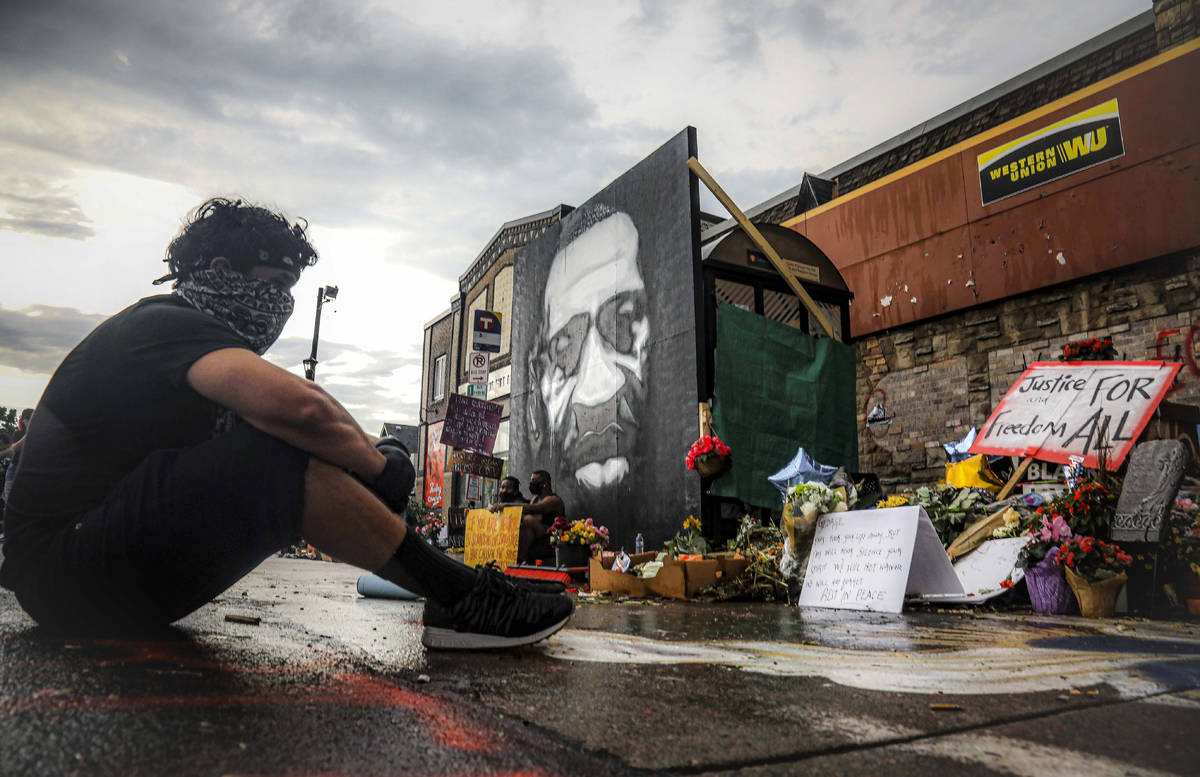 After a new mural, center, of George Floyd is added to a growing memorial of tributes, Trevor R ...