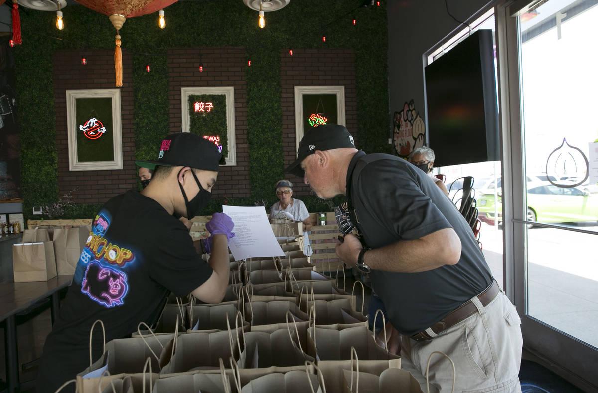 Ronald Duong, employee at Graffiti Bao restaurant, talks with Jim Lewis, a volunteer driver, wh ...