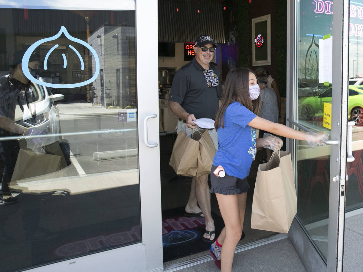 A Volunteer driver, Jim Lewis, and his daughter Izzi, 11, carry bags of food to load into their ...