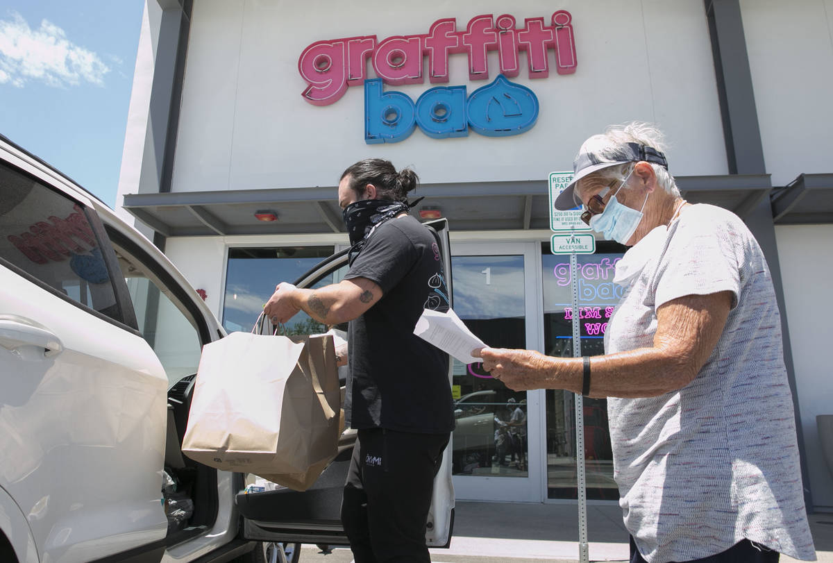 Marc Marrone, chef and owner of Graffiti Bao, loads bags of food into a volunteer driver, Cecil ...