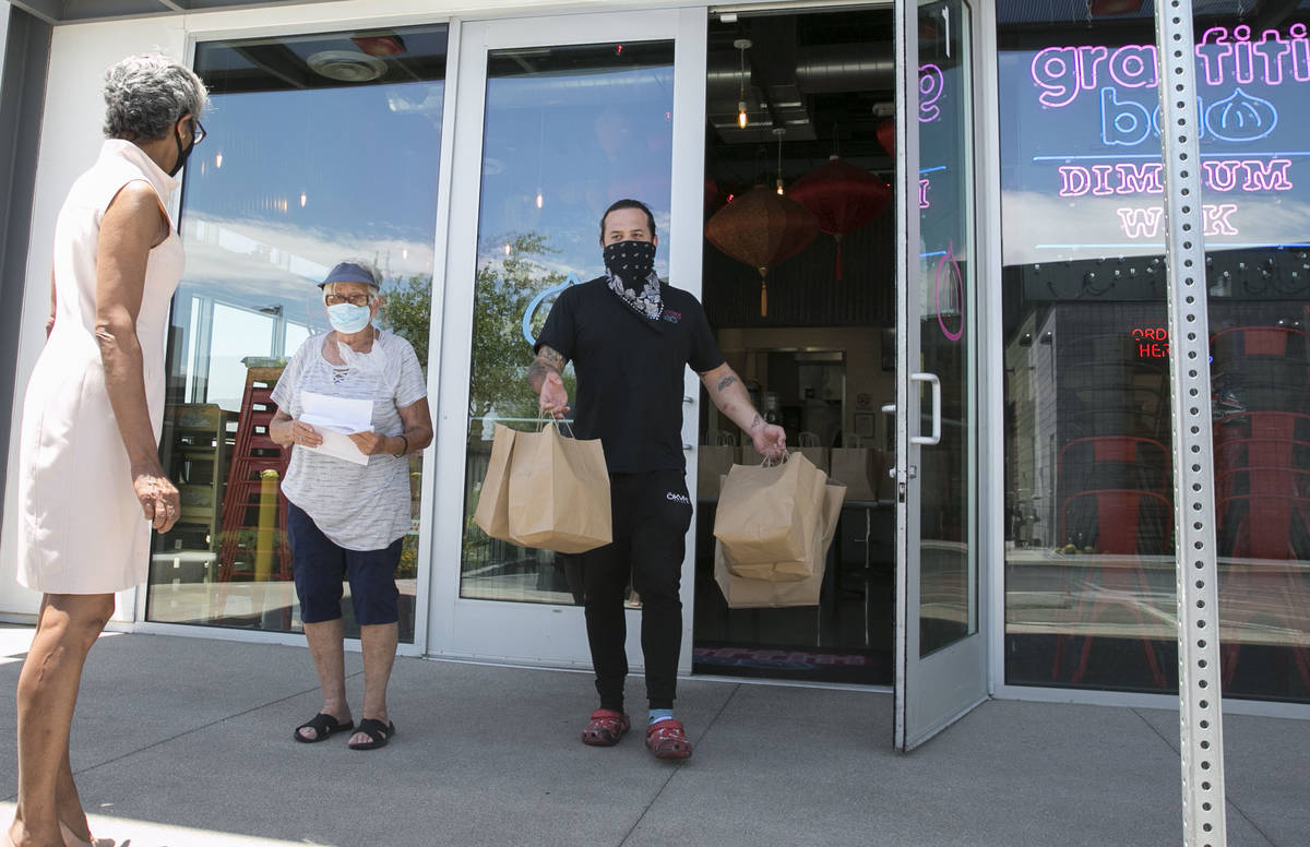 Marc Marrone, chef and owner of Graffiti Bao, carries bags of food with volunteer driver, Cecil ...