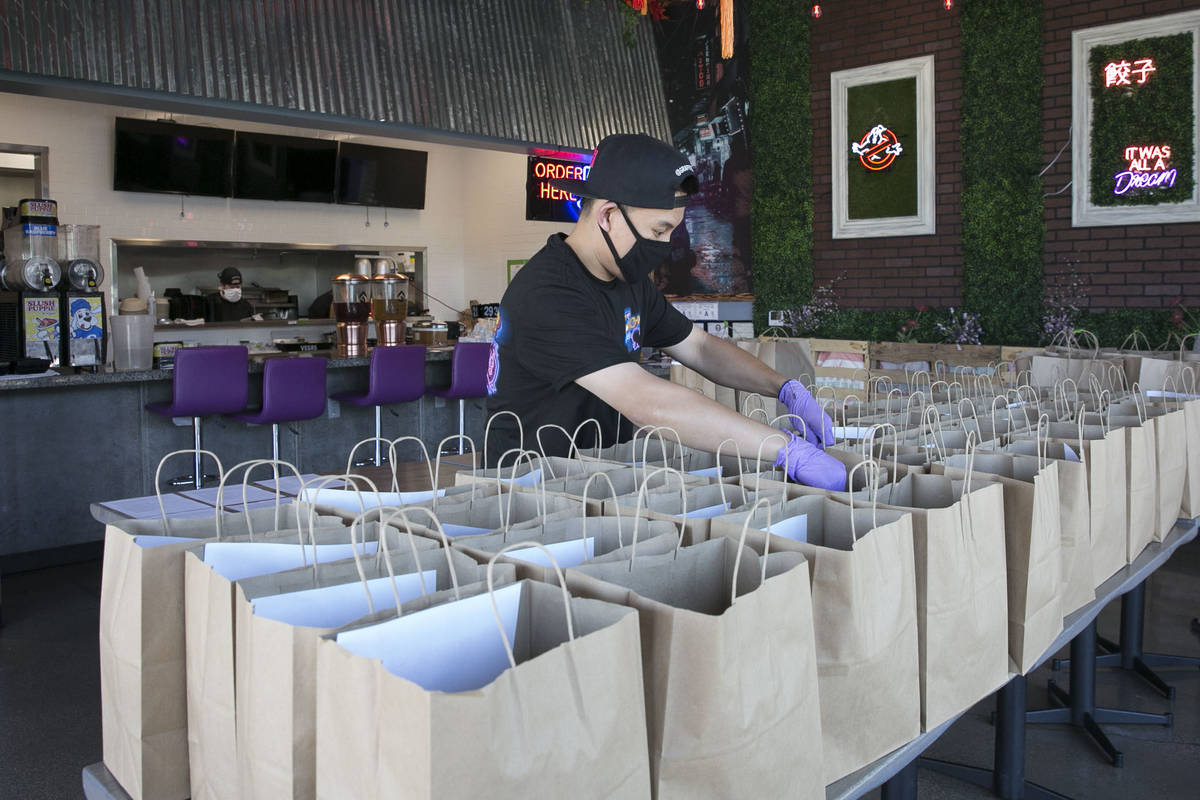 Ronald Duong, employee at Graffiti Bao restaurant, prepares bags of food to be delivered on Fri ...