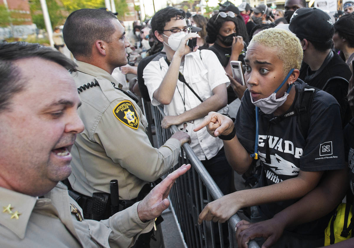 A protester has a heated discussion with assistant sheriff Christopher Jones, bottom/left, outs ...