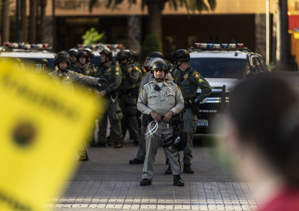 Las Vegas police officers watch protesters pass the Golden Nugget on Wednesday, June 3, 2020, i ...