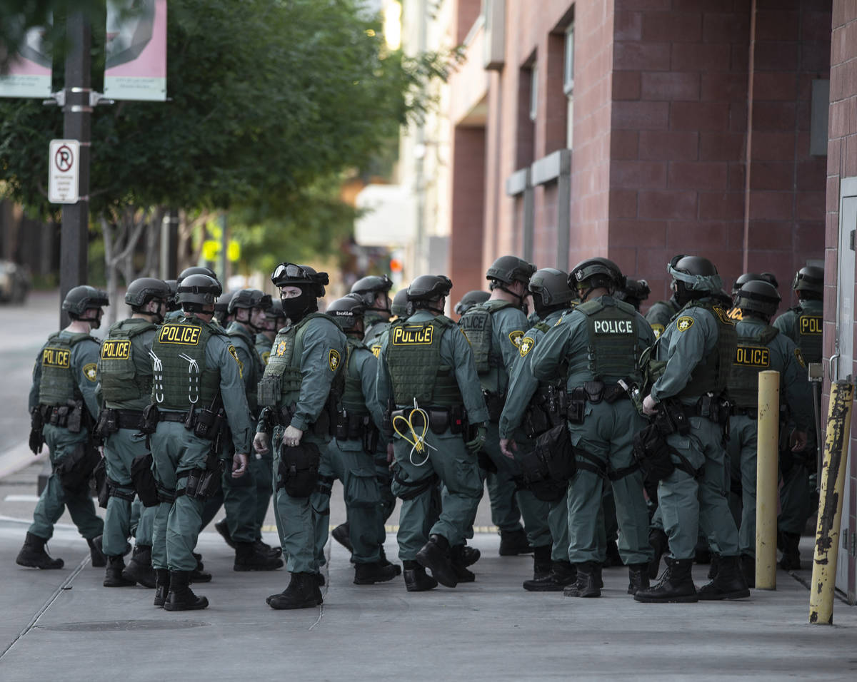 Police officers mobilize in downtown Las Vegas on Wednesday, June 3, 2020, as riots continue th ...