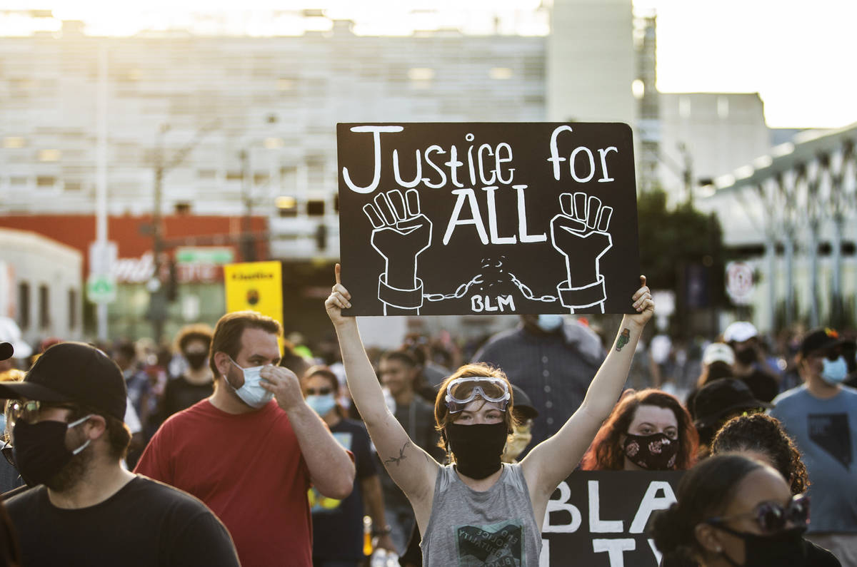 A crowd of at least 300 protesters march in downtown Las Vegas on Wednesday, June 3, 2020, as r ...