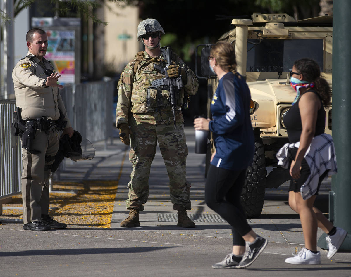 Protesters walk past law enforcement outside Las Vegas City Hall on Wednesday, June 3, 2020, in ...
