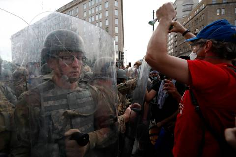 National Guard soldiers walk as they unload from buses as demonstrators gather to protest the d ...