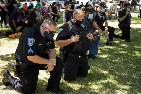 "Fairfield police officers kneel during ""Taking a knee for Justice and Prayer"" service ..."