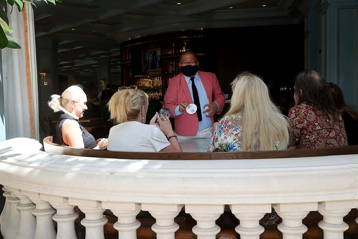 A waiter shows diners a coaster with a QR Code for the menu at Sadelle's Cafe overlooking the C ...