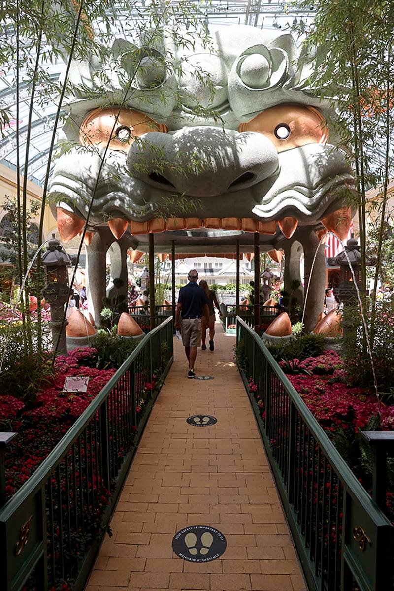Guests maintain social distance inside the Conservatory at the Bellagio on the Strip in Las Veg ...
