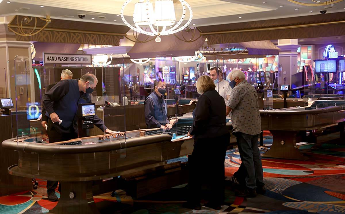 Guests play craps at the Bellagio on the Strip in Las Vegas as the resort reopens after 78 days ...