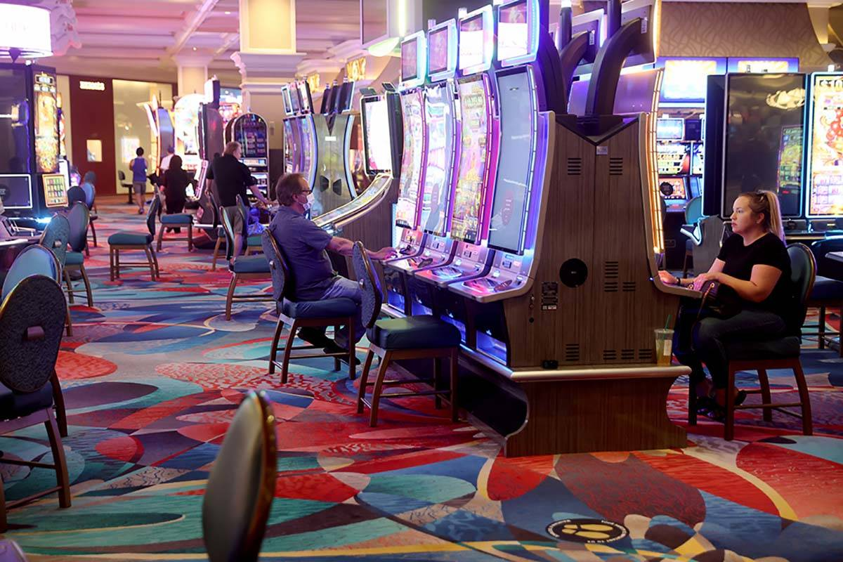 Guests play slots at the Bellagio on the Strip in Las Vegas as the resort reopens after 78 days ...