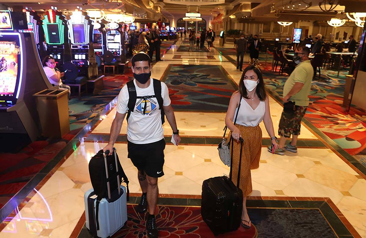 Jorge Aith and his wife Tassia Reis from Brazil head to their room at the Bellagio on the Strip ...