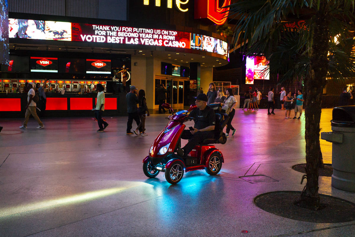 A man rides a scooter along the Fremont Street Experience as hotel-casinos reopen in downtown L ...