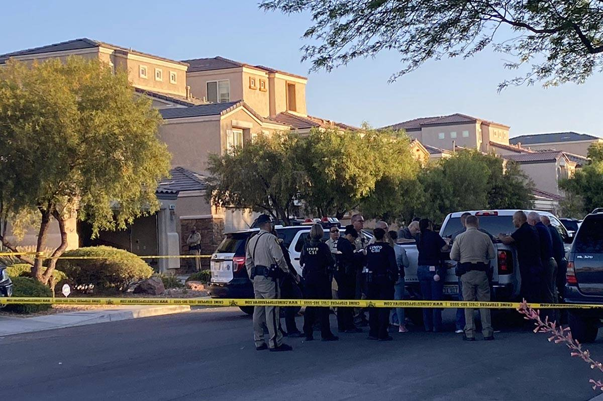 Las Vegas police officers gather at the scene of a homicide in the 8800 block of Canyon Saddle ...